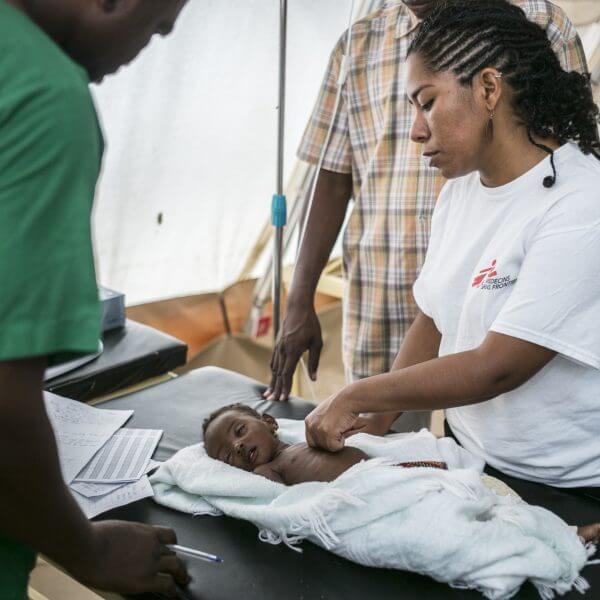 Et lille barn er blevet indlagt på Læger uden Grænsers specialiserede afdeling for underernærede børn i Maiduguri, barnet undersøges af lægen Ebel Lorena Ortiz. Juli 2017. © Sylvain Cherkaoui/Cosmos